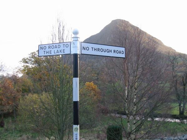 Wainwright's negative signpost at Kirkstile Inn road junction and Mellbreak