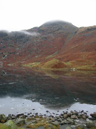 Tarn Crag reflected in a frozen Easedale Tarn