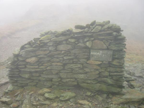 Shelter at Nan Bield Pass with a sign to Mardale and Kentmere