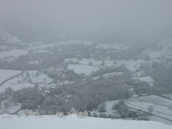 Grasmere village just visible through the snow from high up Helm Crag