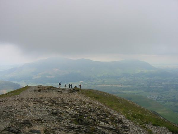 Walkers heading for Grisedale Pike's east ridge, with the cloud building over Skiddaw and Blencathra