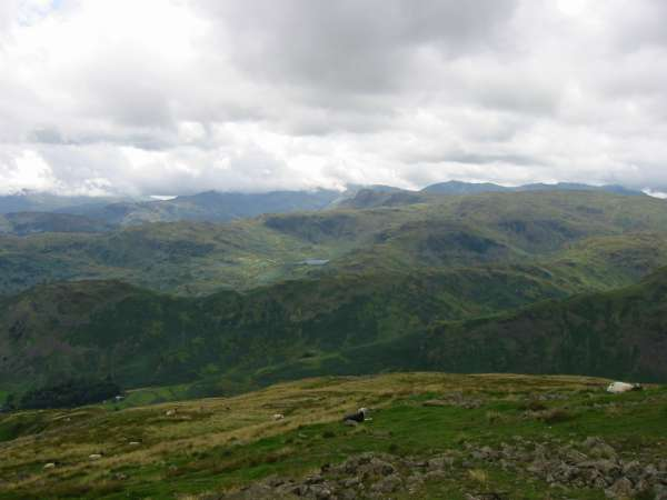 The view west. Easedale Tarn is visible in the middle of the picture and the pointed peak on the skyline right of centre is Bowfell