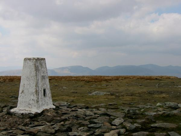 High Street trig point with Fairfield and the Helvellyn ridge in the distance