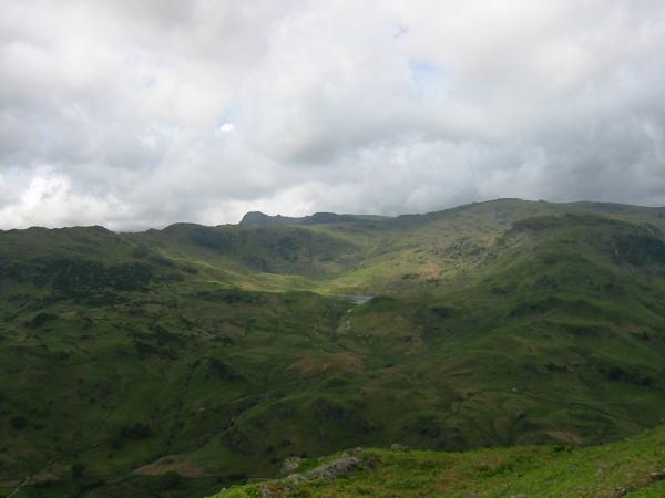 Easedale Tarn just visible across Easedale with Harrison Stickle on the skyline