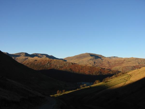 The wooded Hartsop Above How ridge with Fairfield and Saint Sunday Crag behind