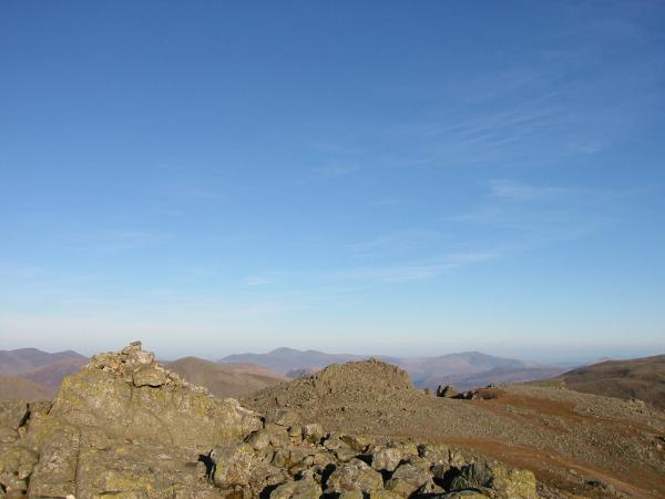 Scafell summit with Symonds Knott just beyond and Skiddaw and Blencathra in the far distance