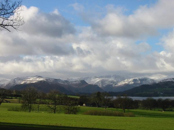The view south towards a snow covered Place Fell and Helvellyn range