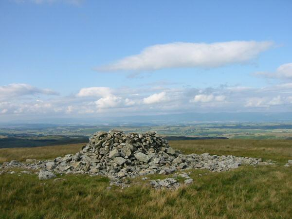 Selside Pike's summit cairn with the Pennines in the distance
