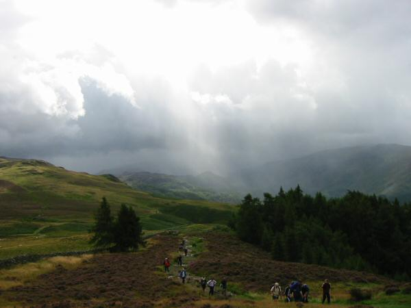 A large group approaches Walla Crag summit from the south, along with the rain