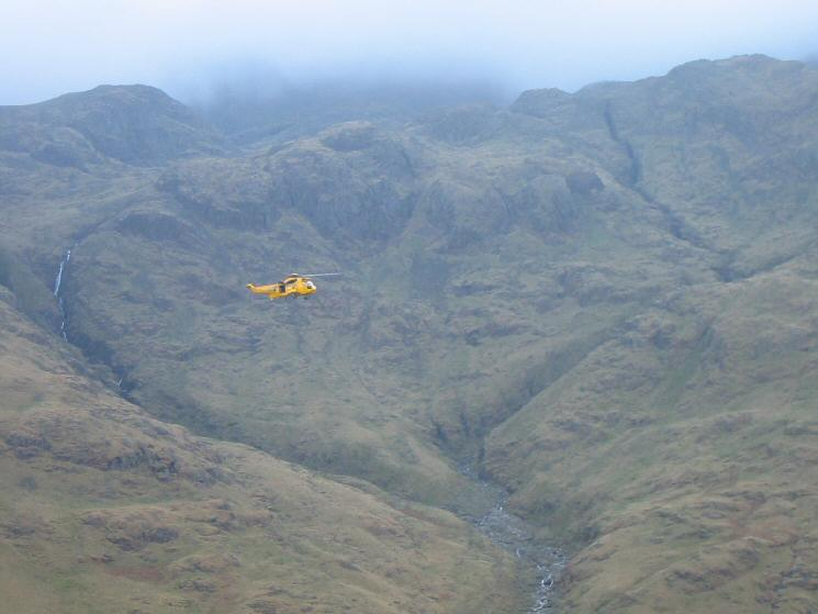 A rescue helicopter, out training, passing in front of Piers Gill