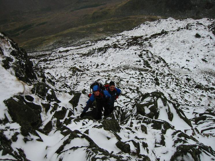 Ascending some steep snow covered rocks on our route up Haystacks from Scarth Gap