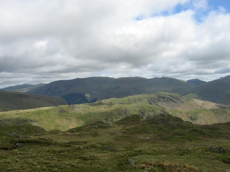 Calf Crag and Steel Fell in sunshine with the Helvellyn ridge and Saint Sunday Crag behind