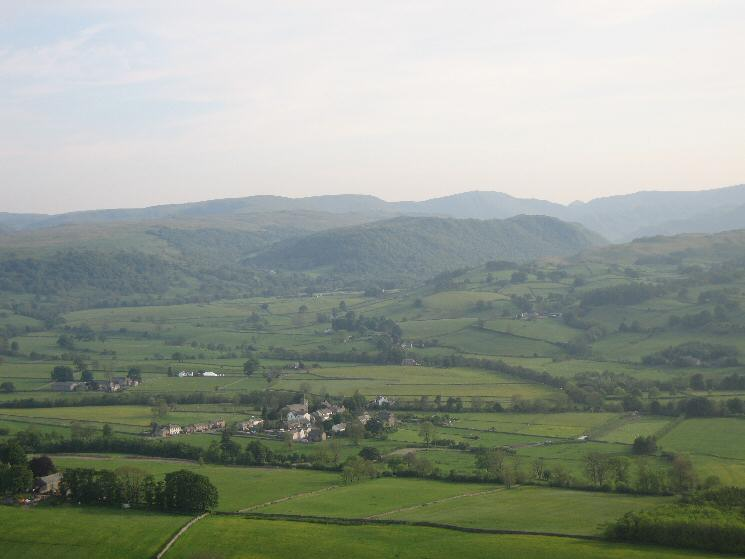 Looking over Bampton Grange to Naddle Forest with the High Street fells behind from Knipescar Common