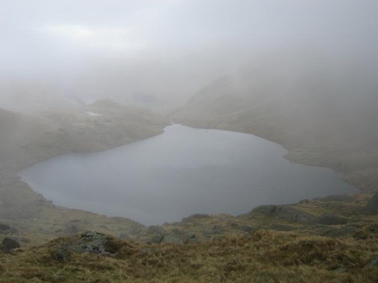Small Water comes into view as we drop out of the cloud on the descent from Nan Bield Pass