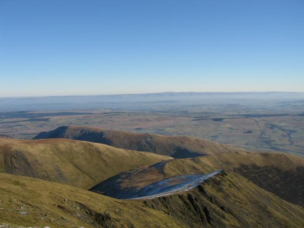 Looking back down on Scales Fell and Souther Fell from Blencathra's summit with the North Pennines in the distance across the Vale of Eden