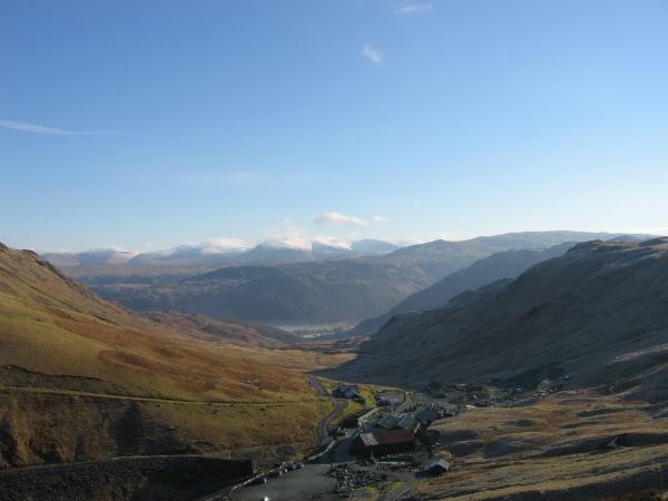 Looking back down on Honister Pass with a snowy Helvellyn ridge in the distance