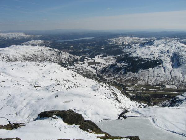 Great Langdale and Windermere with a frozen Stickle Tarn directly below from Pavey Ark's summit