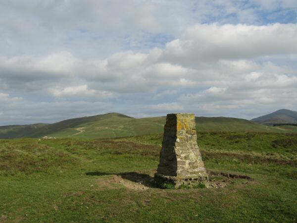 Ling Fell trig point with Broom Fell on its left and Grisedale Pike on the far right