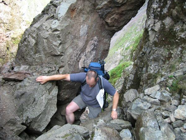 Climbing under the boulder at the top of the first section of Lord's Rake