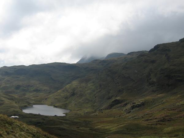 Codale Tarn with Harrision Stickle partly in cloud in the distance behind the Blea Rigg ridge