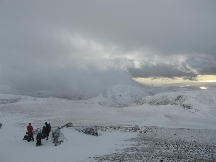 Helvellyn's summit shelter with Fairfield in the cloud