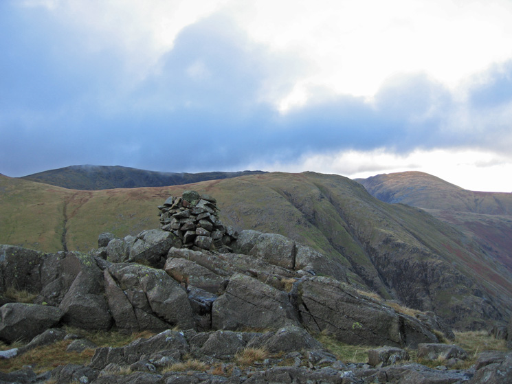 The cairn at the 601m top of Seathwaite Fell with Base Brown behind