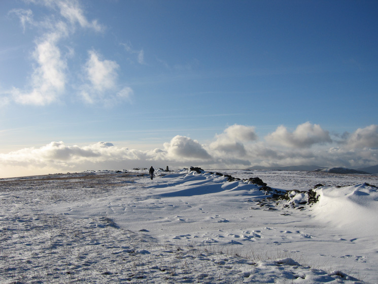 A walker approaching the trig point at High Street's summit