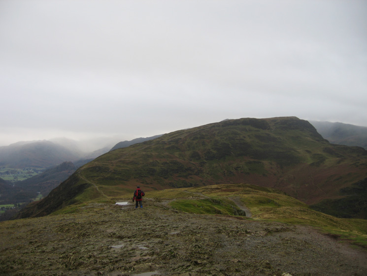 A lone walker leaving Catbells' summit with Maiden Moor ahead