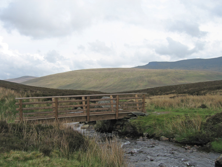 The footbridge across the infant River Caldew with Mungrisdale Common in sunshine and Blencathra in shade