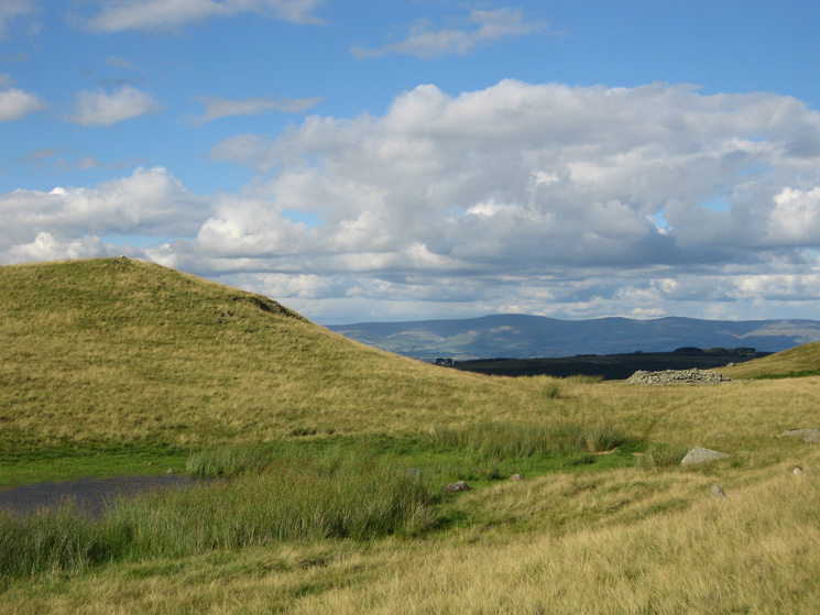 The small tarn and the prehistoric round cairn next to Four Stones Hill