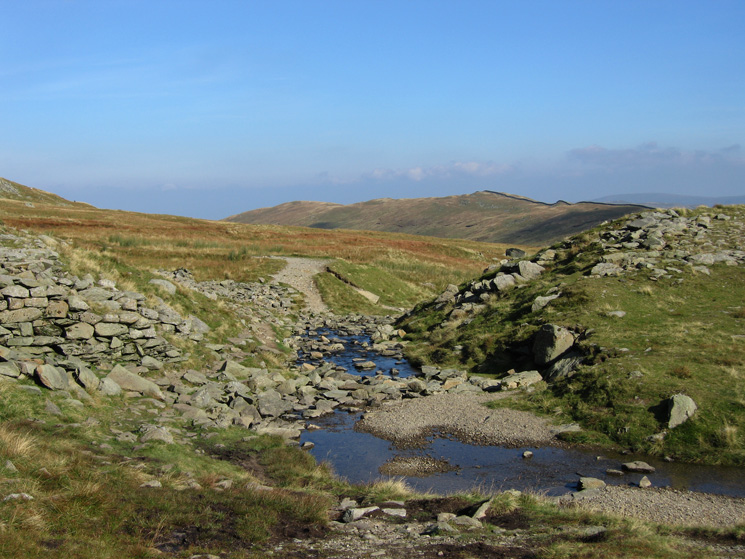 Red Tarn Beck as it leaves Red Tarn with Birkhouse Moor in the distance