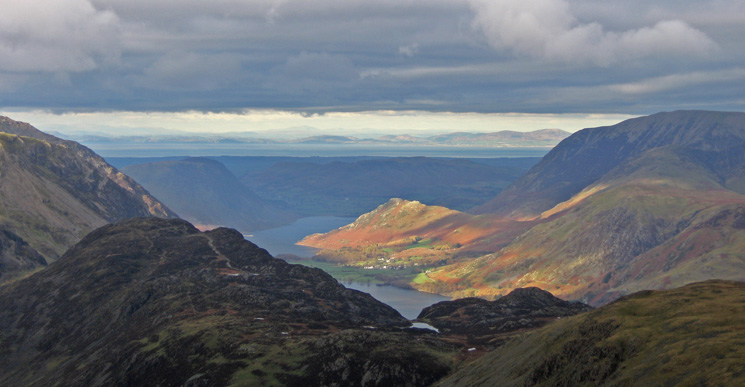 Rannerdale Knotts catches the sun with Scotland across the Solway Firth in the distance
