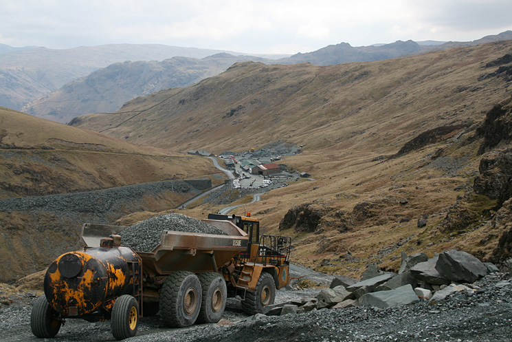 A quarry truck heads down to the mine buildings