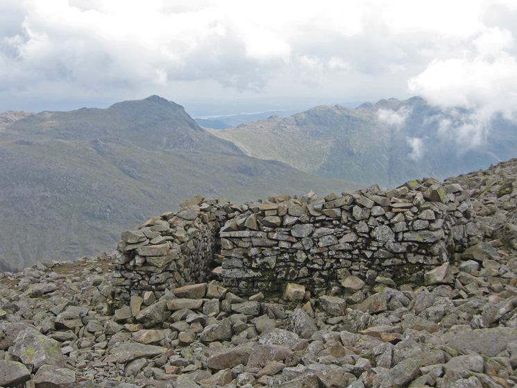 The remains of the old tea house (probably) at Scafell Pike's summit with Bowfell beyond