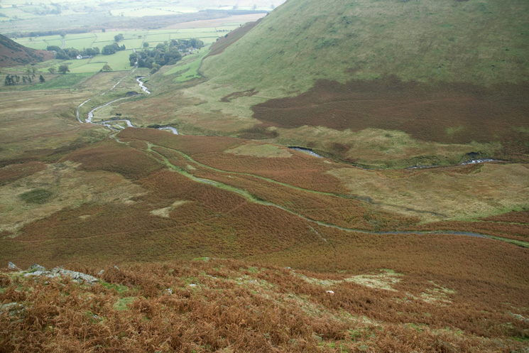 Looking back down the steep ascent, Mungrisdale village is in the trees