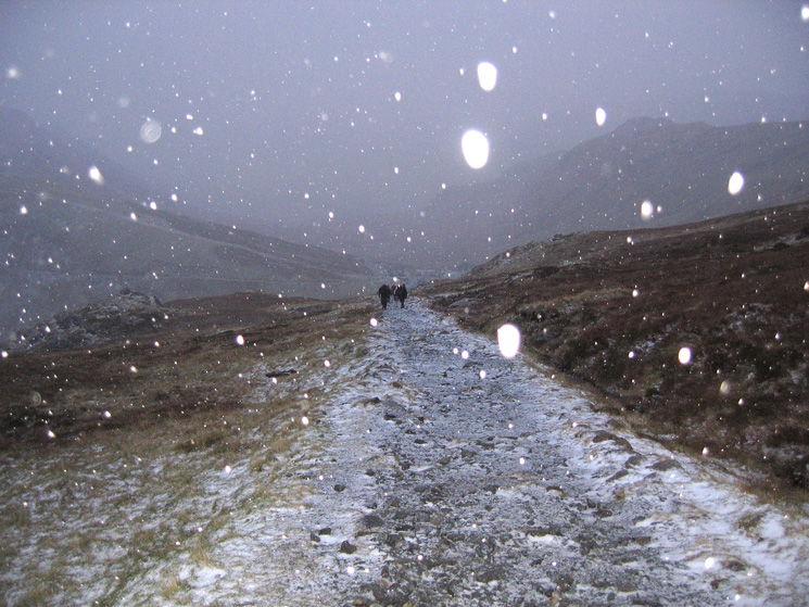 The camera's flash highlights the hail as I look back to Honister while on my way to the Drum House
