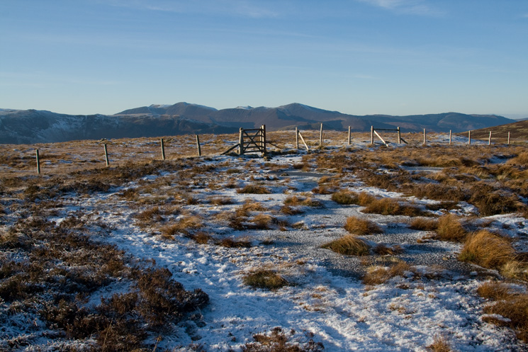 The gate at High Tove's summit with the north western fells in the distance