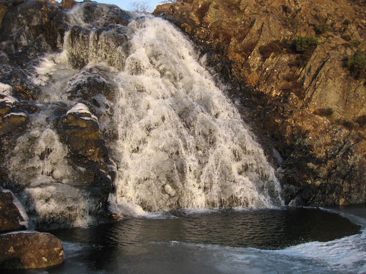 A partly frozen waterfall in Sourmilk Gill