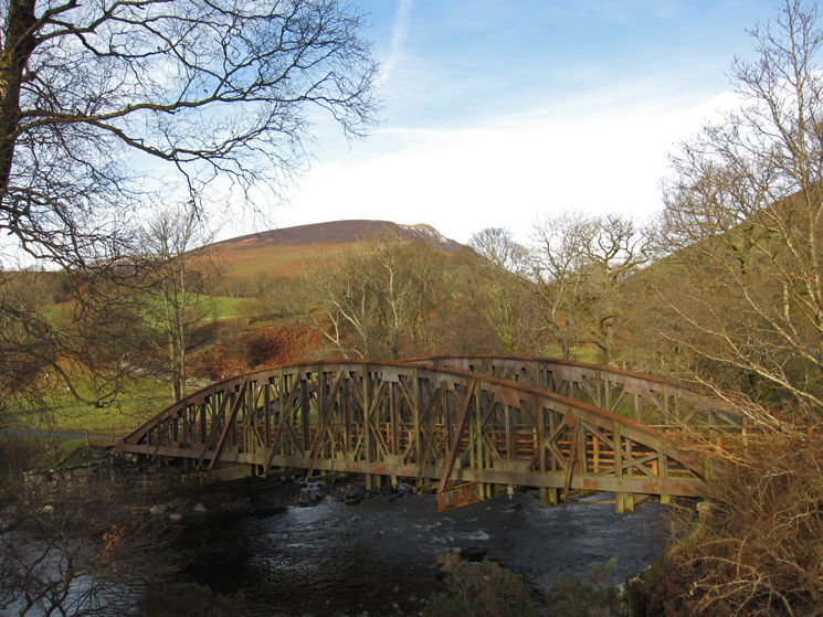 One of the many bridges over the River Greta on the old railway line with Lonscale Fell behind