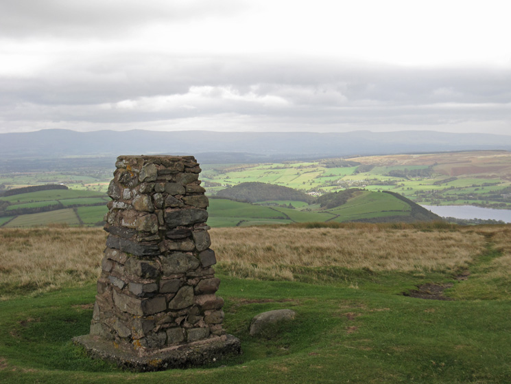 Little Mell Fell's trig point with the North Pennines in the distance and a glimpse of Ullswater