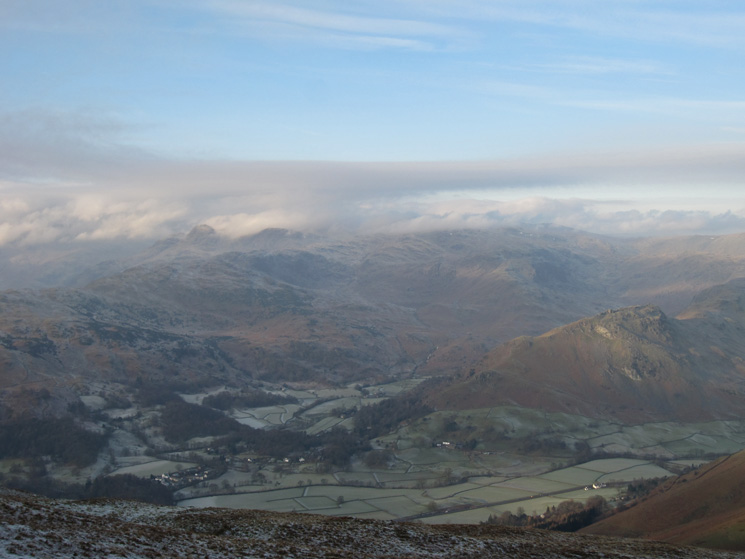 The Langdale Pikes partly in cloud, Grasmere village in the valley below and Helm Crag on the right