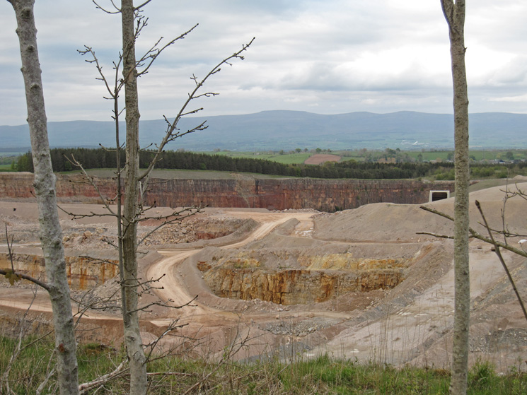 Looking over the wall at the southeast end of Knipescar Common to see Shapbeck Quarry and the North Pennines