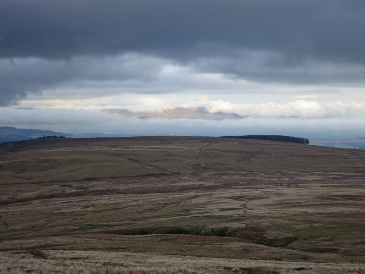 A gap in the clouds reveals the North Pennines above Heughscar Hill