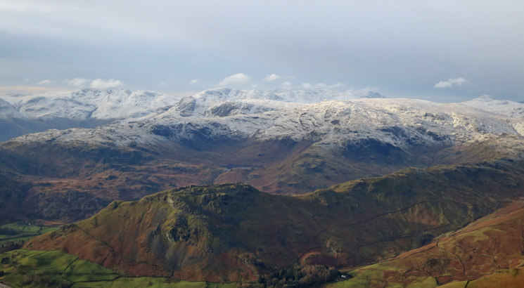Helm Crag with snow on the higher fells beyond