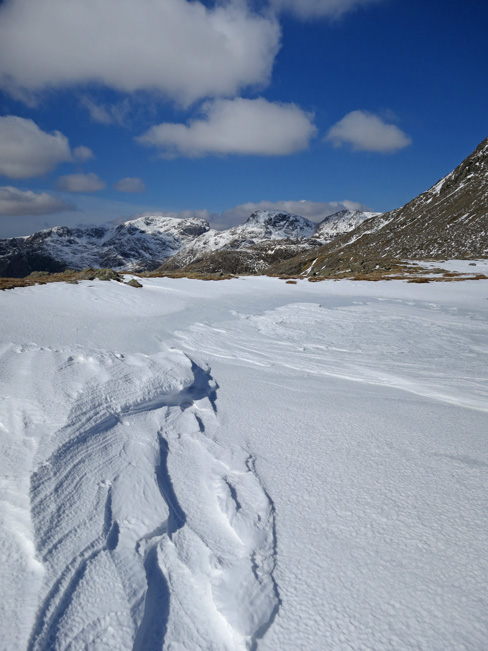 The Scafells from a frozen and snow covered tarn at Three Tarns